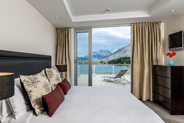 large comfortable double bed with clean sheets in master bedroom of 3 Bedroom Apartment with private hotel balcony outside and breathtaking views of The Remarkables at Oaks Club Resort, Queenstown, New Zealand