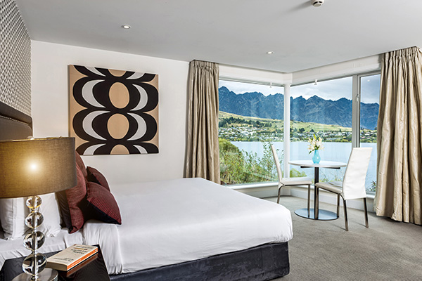comfortable double bed with fluffy pillows and clean sheets facing large windows with views of The Remarkables mountain range and Lake Wakatipu in Queenstown during summer