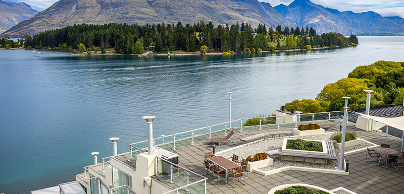 aerial view of The Remarkables mountain range and jet boats on Lake Wakatipu in Queenstown from private courtyard of Hotel Room holiday apartment at Oaks Club Resort