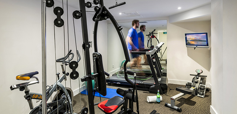 hotel guest running on treadmill in fully equipped gym with weights and rowing machine in Queenstown, New Zealand