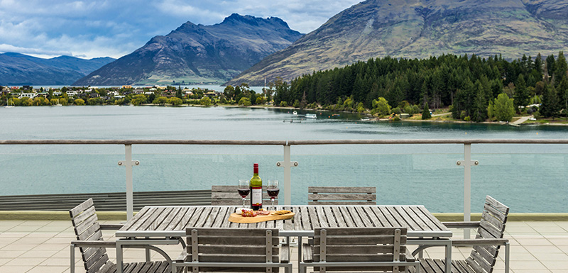 Vegetarian menu option and bottle of wine on table on large private balcony of hotels in Queenstown at Oaks Club Resort hotel, Queenstown, New Zealand