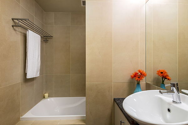 clean en suite bathroom with bath tub, shower, toilet and fresh towels for guests staying in 1 Bedroom holiday apartment at Oaks Shores hotel in Queenstown, New Zealand