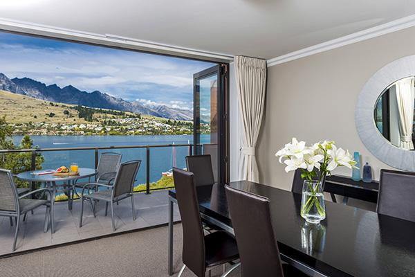 large dining table in spacious 1 bedroom holiday apartment with private balcony at Oaks Shores hotel in Queenstown, New Zealand
