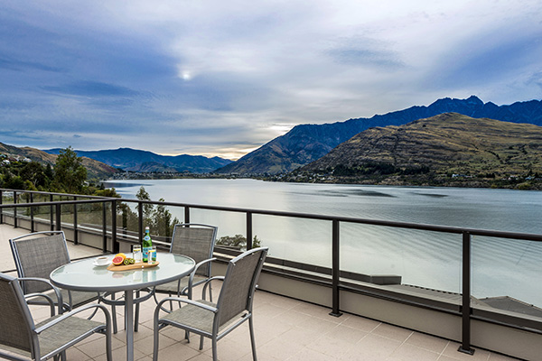 spacious penthouse balcony with vegetarian food menu option on table and panoramic views of Lake Wakatipu in Queenstown, New Zealand