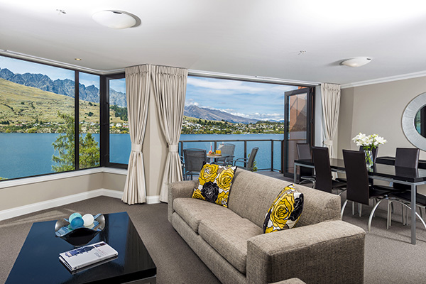 big living room with dining table, chairs, couches and Wi-Fi access in 4 Bedroom Penthouse holiday accommodation at Oaks Shores hotel in Queenstown, New Zealand