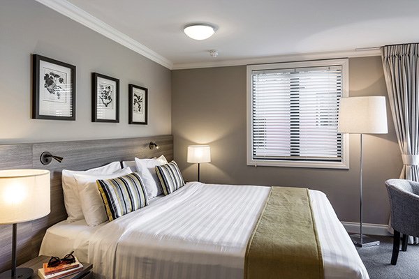 close up view of queen size bed in bedroom with table and office chair for corporate travellers to do work on while visiting Queenstown on a business trip