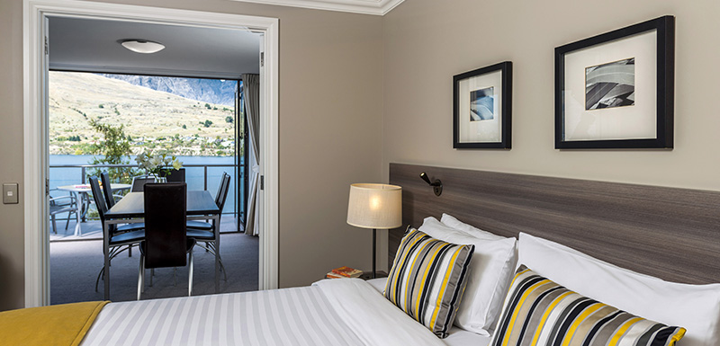 comfortable large king size bed with clean sheets and pillows in master bedroom of penthouse holiday apartment in Queenstown, New Zealand