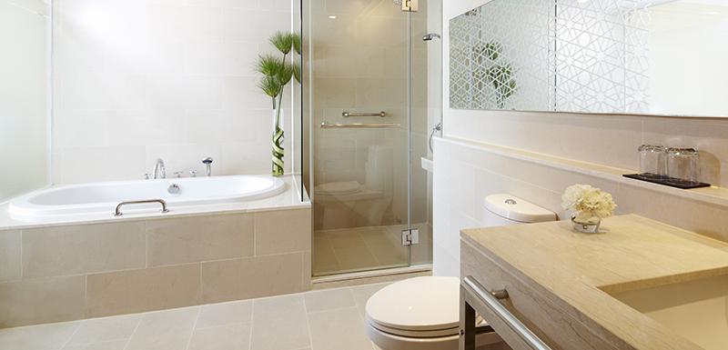 large en suite bathroom with toilet, bathtub, shower and clean towels in 1 bedroom holiday apartment at Oaks Bangkok Sathorn hotel in Thailand