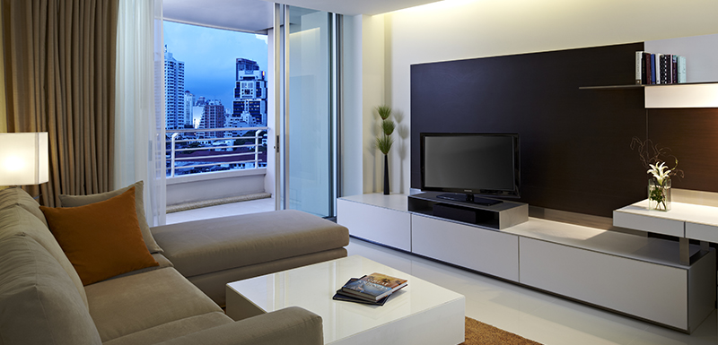 comfortable couches and large plasma satellite TV with international channels in air conditioned living room of Three Bedroom Apartment suite at Oaks Bangkok Sathorn hotel in Thailand