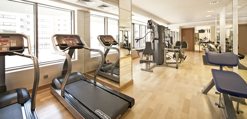 fully equipped gymnasium with treadmills, weights, bench press, rowing machine and air conditioning at Oaks Liwa Executive Suites hotel in Abu Dhabi, United Arab Emirates