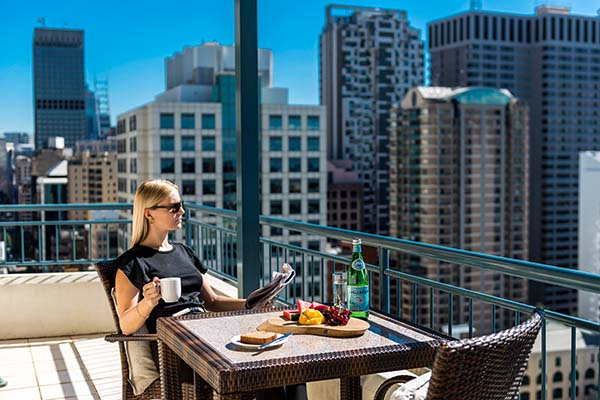 corporate traveller at serviced apartments Sydney on business trip enjoying cup of coffee and breakfast on balcony of 3 bed apartment with views of Sydney CBD