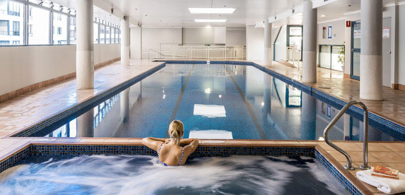 Sydney city hotels visitor relaxing in indoor swimming pool and jacuzzi at Oaks on Castereagh in Sydney CBD, Australia