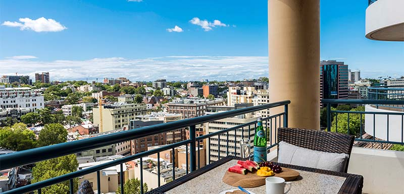 Hotel Balcony With Chairs And Table Fruit Bowl Views Of Brisbane City At The