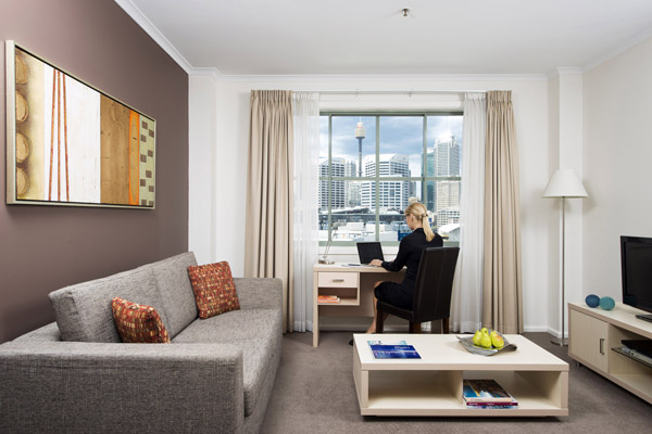 business traveller typing on laptop at window of 1 bedroom hotel apartment near Darling Harbour