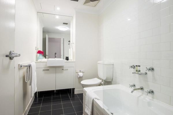 en suite bathroom with bath tub, toilet, mirror and clean towels