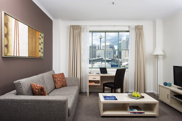 large lounge room at Oaks Goldsbrough Apartments with views of Darling Harbour and work space including desk for business travellers visiting Sydney