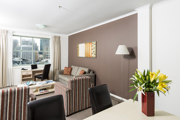 living room area in 2 bedroom hotel apartment walking distance to Darling Harbour with views of city and modern furniture