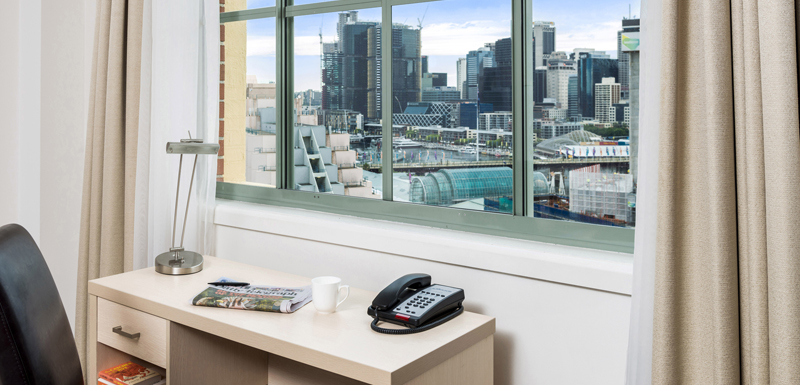 desk for corporate travellers with views out window of Darling Harbour and Sydney city skyline