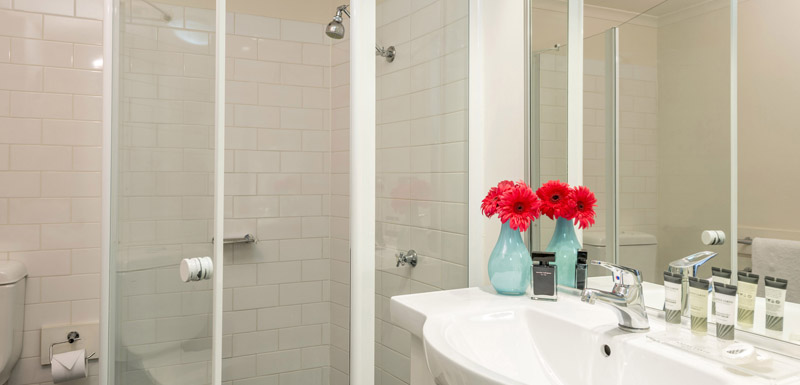 en suite bathroom in studio apartment and Oaks Goldsbrough Apartments in Sydney city centre with large shower and toilet