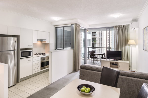 spacious living room with air conditioning and balcony in 1 bedroom apartment in Brisbane CBD