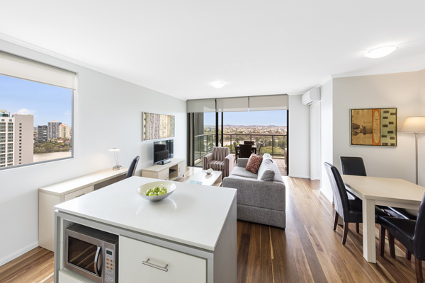 living room leading out to large balcony at Oaks 212 Margaret St hotel in Brisbane CBD with views of Brisbane River