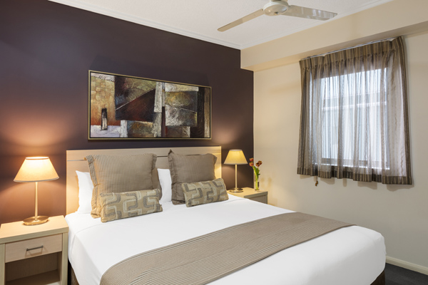 queen size bed in 2 bedroom apartment with ceiling fan and air conditioning in Brisbane city