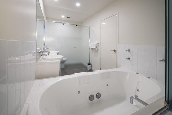large bathtub and jacuzzi in modern en suite bathroom at Oaks 212 Margaret Street hotel in Brisbane city centre