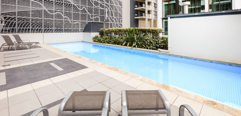 outdoor swimming pool area at Oaks 212 Margaret Street hotel in Brisbane city with sun loungers