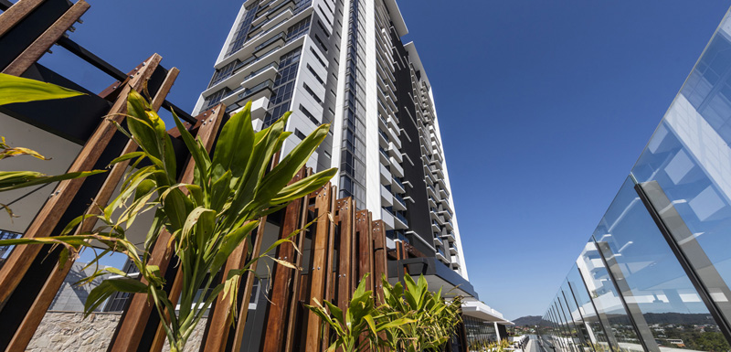 exterior view of The Milton Brisbane hotel building in summer with blue skies in background