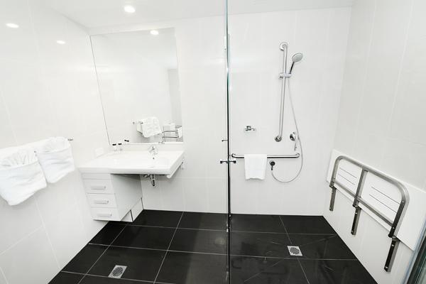 en suite bathroom with disabled access shower in studio hotel room at Oaks Grand Gladstone, Queensland, Australia