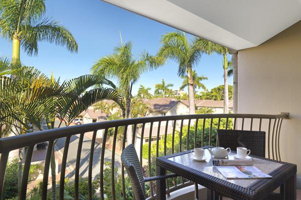 private balcony with table and chairs in one bedroom executive apartment at Oaks Oasis Resort hotel in Caloundra, Sunshine Coast