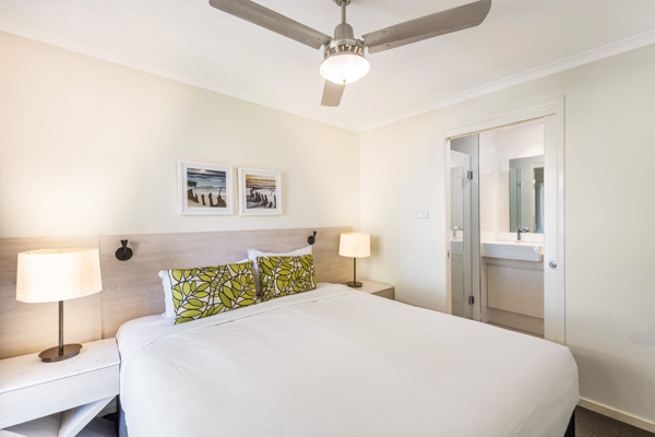 master bedroom with en suite bathroom, air conditioning, Wi-Fi and ceiling fan in 3 bedroom villa at Oaks Oasis Resort hotel on Sunshine Coast, Queensland