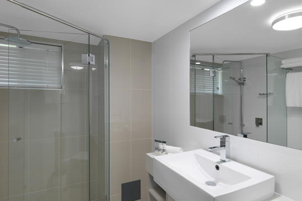 Executive Studio hotel apartment en suite bathroom with toilet, shower and large mirror at Oaks Oasis Resort in Caloundra on Sunshine Coast, Queensland, Australia