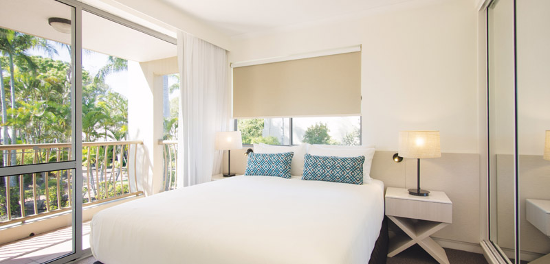 air conditioned bedroom with private balcony and big wardrobes with plenty of storage space at Oaks Oasis Resort in Caloundra