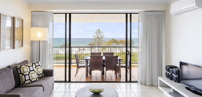 balcony with tables and chairs overlooking beach and ocean in 2 bedroom air conditioned apartment at Oaks Seaforth Resort hotel, Sunshine Coast, Queensland, Australia