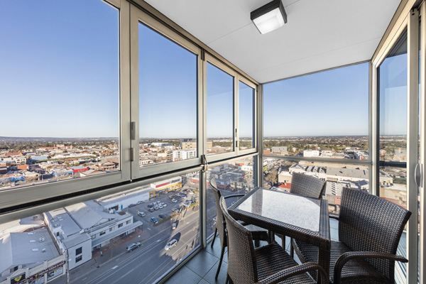 balcony at hotel Adelaide CBD with large windows, table, chairs and panoramic views of Adelaide city at iStay Precinct hotel near Adelaide Oval AFL stadium