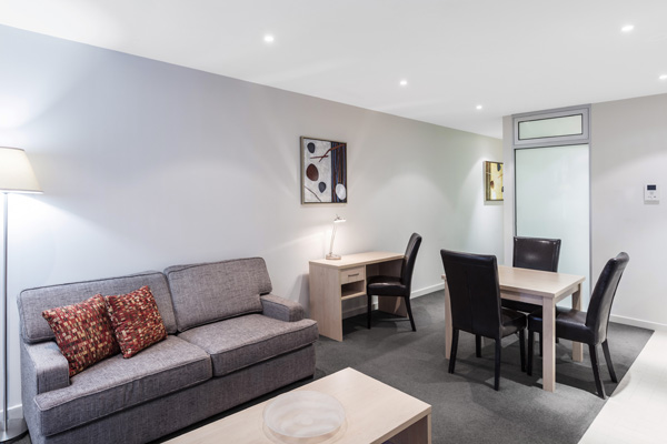 Adelaide hotels spacious living room with dining table, chairs, couches and Wi-Fi access in 1 bedroom apartment at iStay Precinct hotel
