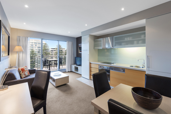 big living room with air conditioning, Foxtel on TV and 30 minutes free Wi-Fi in 1 bedroom park view apartment at Oaks Plaza Pier hotel on Glenelg Beach, South Australia