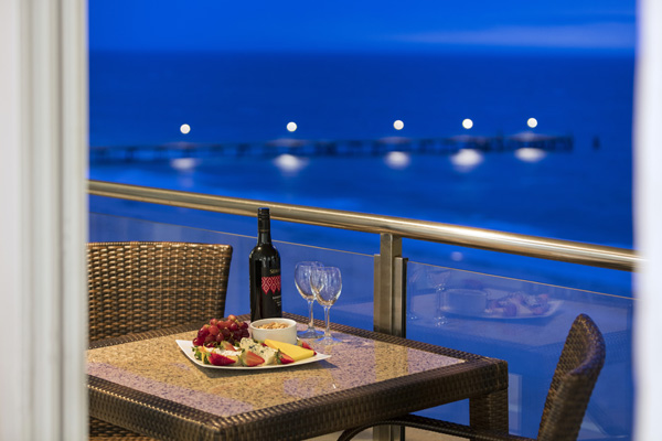 bottle of wine, cheese and biscuits on balcony in evening with views of ocean at beachfront hotel in Glenelg, SA