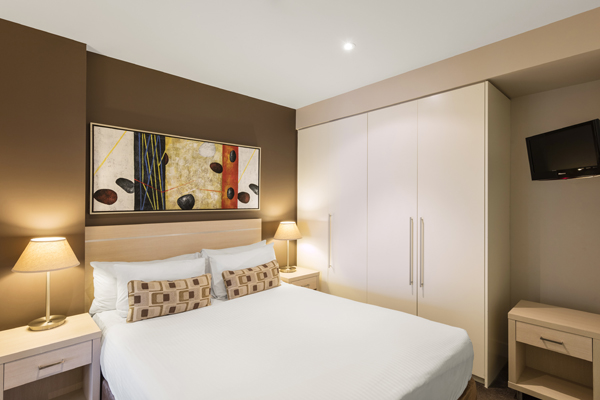 queen size bed, large wardrobe with lots of storage and TV with Foxtel in air conditioned 2 Bedroom Apartment at Oaks Plaza Pier hotel in Glenelg, South Australia