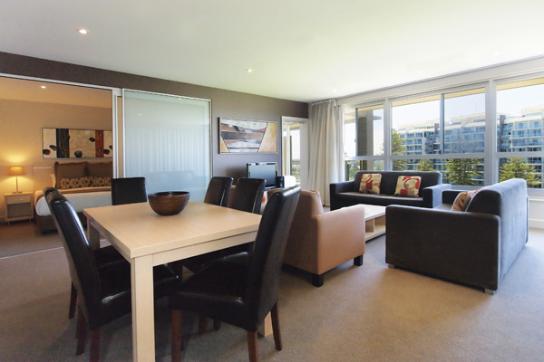 Accommodation Glenelg open plan living room dining area with large table, chairs and air con in 3 Bedroom Apartment near beach in Glenelg, South Australia
