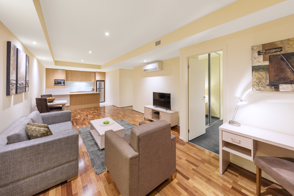 living room with polished wood floors, comfortable couches and TV with Foxtel in air conditioned 1 bedroom hotel apartment with Wi-Fi at Oaks on Lonsdale Street, Melbourne city, Victoria, Australia