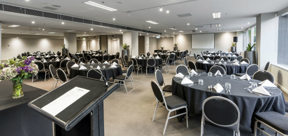 front of event room for hire ready for conference with tables, chairs and large speakers in Melbourne city