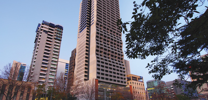 external view of Oaks On William serviced apartments in Melbourne at sunrise from Flagstaff Gardens public park in Melbourne CBD, Victoria, Australia