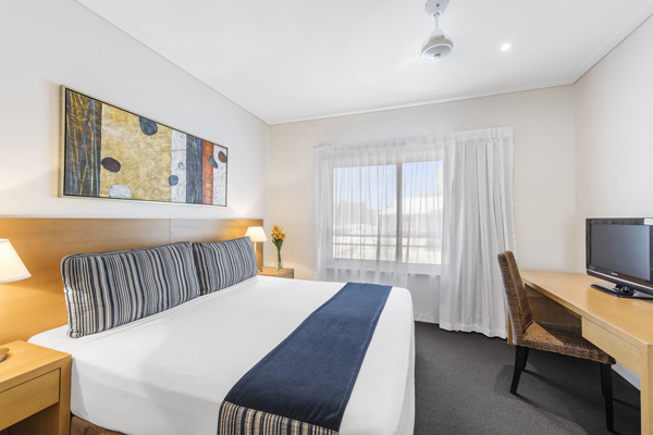 comfortable double bed with Foxtel on TV in front and sliding glass doors leading to private balcony in 2 bedroom apartment at Oaks Broome hotel, Western Australia