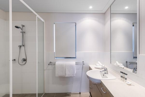 clean en suite bathroom of Oaks Broome hotel room with shower, toilet and fresh white towels in Western Australia