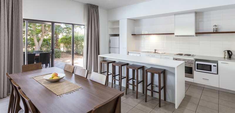 large kitchen with modern appliances including microwave, oven and kettle in air conditioned hotel apartment in Broome, Western Australia
