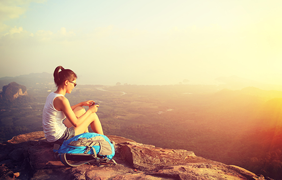 Young woman sitting on Wolfgang Peak hike view mountain near Moranbah accommodation close to Oaks Moranbah hotels at sunset during vacation to Queensland, Australia