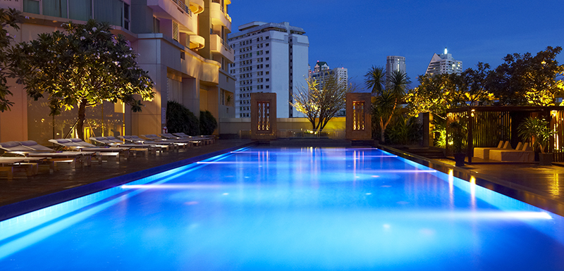hotel guests swimming in large lap pool at Oaks Bangkok Sathorn during the evening with views of Thailand in background