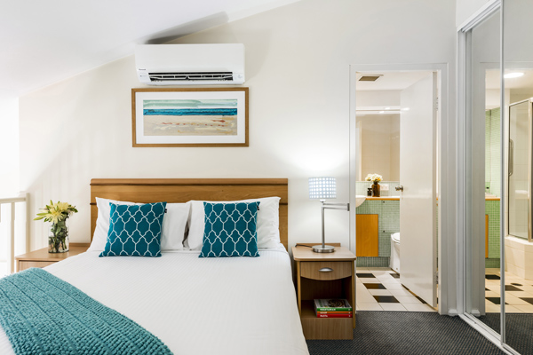 en suite hotel room in The Entrance New South Wales with white sheets and blue pillows